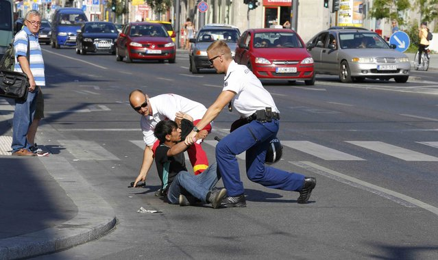 Hungarian police officers detain a migrant in the middle of a street in Budapest, Hungary September 2, 2015. (Photo by Laszlo Balogh/Reuters)