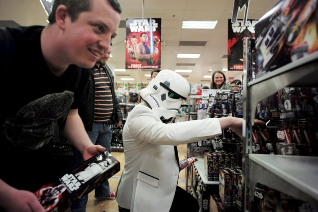 """A shopper wearing an Imperial Stormtrooper helmet picks new toys from the upcoming film """"Star Wars: The Force Awakens"""" on """"Force Friday"""", just after midnight on 'Force Friday' in Sydney, September 4, 2015. (Photo by Jason Reed/Reuters)"""