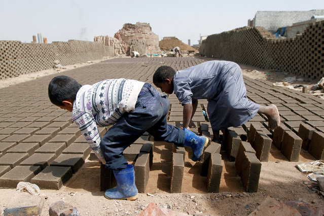 Boys arrange blocks at a brick factory on the outskirt of Sanaa, Yemen May 28, 2016. (Photo by Mohamed al-Sayaghi/Reuters)
