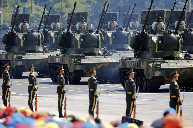China's People's Liberation Army (PLA) soldiers on their armoured vehicles equipped with anti-aircraft artillery roll to Tiananmen Square during the military parade marking the 70th anniversary of the end of World War Two, in Beijing, China, September 3, 2015. (Photo by Damir Sagolj/Reuters)