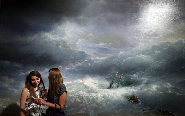 "Visitors stand in front of the painting ""A Wave"" by Russian artist Ivan Aivazovsky displayed in the Tretyakov Gallery on Krymsky Val in Moscow, Russia, 28 July 2016. The exhibition is open from 29 July to 20 November. (Photo by Yuri Kochetkov/EPA)"