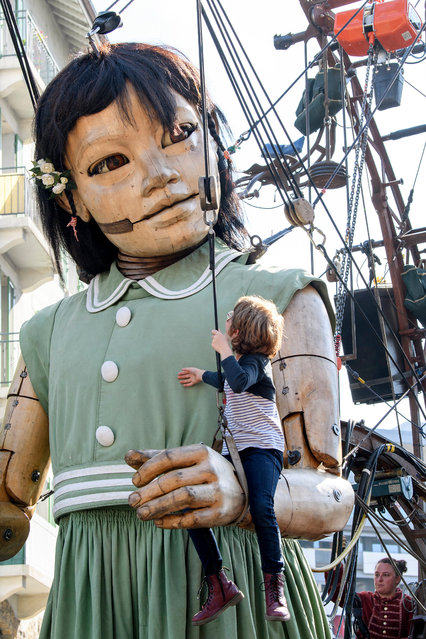 "A child play on the arms of a little giant puppet before parading through the spectators during the ""The Saga of the Giants"" street theatre, in Geneva, Switzerland, 29 September 2017. The giants of the Royal de Luxe Company guest in Geneva on the theme ""The Knight of the Lost Time"" from 29 September to 01 October 2017. (Photo by Martial Trezzini/EPA/EFE)"
