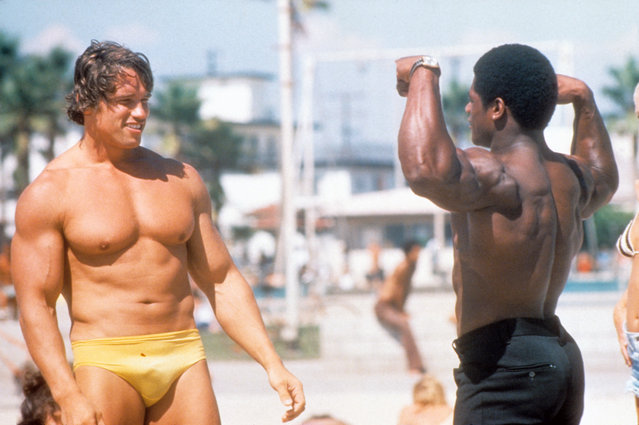 Austrian Bodybuilder Arnold Schwarzenegger admires another bodybuilder at Muscle Beach in Venice in August 1977 in Los Angeles, California. (Photo by Michael Ochs Archives/Getty Images)