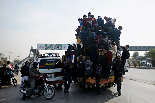 Pakistani students climb on a passenger bus on a high way in Islamabad on January 21, 2013. (Photo by Asif Hassan/AFP Photo)