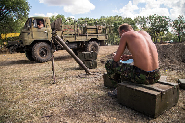 """Ukrainian servicemen rest near their military equipment inside a military camp in the Donetsk region, on August 29, 2014.. NATO chief Anders Fogh Rasmussen urged Russia on August 29 to halt its """"illegal"""" military actions in Ukraine, accusing it of a """"dangerous"""" attempt to destabilise its western neighbour. The conflict raging in eastern Ukraine has killed nearly 2,600 people, the United Nations said on August 29, voicing concern about atrocities committed by armed groups and the increasing involvement of foreign fighters. (Photo by Oleksandr Ratushniak/AFP Photo)"""