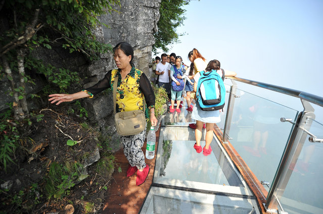 Tourists walk on the 100-meter-long and 1.6-meter-wide glass skywalk clung the cliff of Tianmen Mountain (or Tianmenshan Mountain) in Zhangjiajie National Forest Park on August 1, 2016 in Zhangjiajie, Hunan Province of China. The Coiling Dragon Cliff skywalk, featuring a total of 99 road turns, layers after another, is the third glass skywalk on the Tianmen Mountain (or Tianmenshan Mountain). (Photo by VCG/VCG via Getty Images)