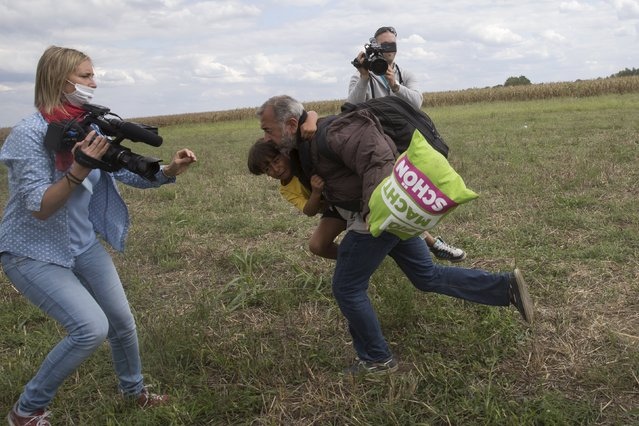 A migrant runs with a child before tripping on a TV camerawoman (L) and falling as he tries to escape from a collection point in Roszke village, Hungary, September 8, 2015. (Photo by Marko Djurica/Reuters)