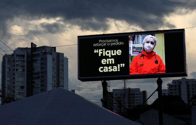"""A sign that reads """"Stay at Home"""" is seen in front of the 28 de Agosto hospital during a demonstration in tribute to healthcare professionals who died from the coronavirus disease (COVID-19) amid the COVID-19 outbreak in Manaus, Brazil, May 16, 2020. (Photo by Bruno Kelly/Reuters)"""