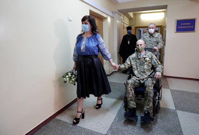 Ihor Ponomarchuk, a Ukrainian serviceman injured in a military conflict in the country's eastern regions, and his bride Anna Diolomina wearing protective face masks arrive for a wedding ceremony at the Main Military Clinical Hospital amid the coronavirus disease (COVID-19) outbreak in Kiev, Ukraine on May 2, 2020. (Photo by Valentyn Ogirenko/Reuters)