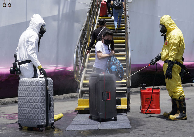 Government workers spray disinfectant on luggage of disembarking Filipino overseas workers at a seaport in Cebu City, Philippines, 23 May 2020. According to the Philippine Coast Guard (PCG), close to 15,000 Overseas Filipino Workers (OFW) in various quarantine centers have been issued clearances to travel to their home towns after they were tested negative for the novel coronavirus and COVID-19 disease and completed the mandatory 14-day facility-based quarantine. (Photo by Jay Rommel Labra/EPA/EFE/Rex Features/Shutterstock)