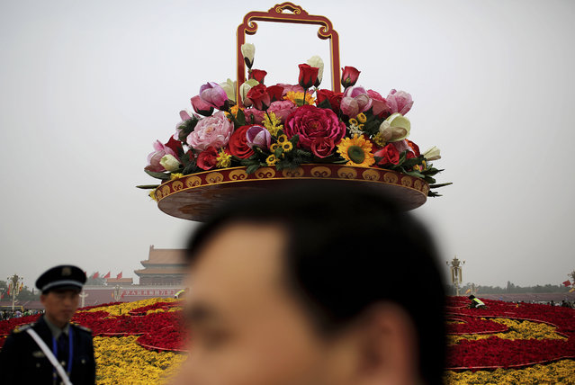 A man walks past workers installing cables on a giant basket decorated with replicas of flowers on display at Tiananmen Square in Beijing, China Thursday, September 25, 2014. Hundreds of thousands of foreign and domestic tourists are expected to flock to the square to celebrate National Day, the 65th anniversary of the founding of the People's Republic of China, on Oct. 1. (Photo by Andy Wong/AP Photo)