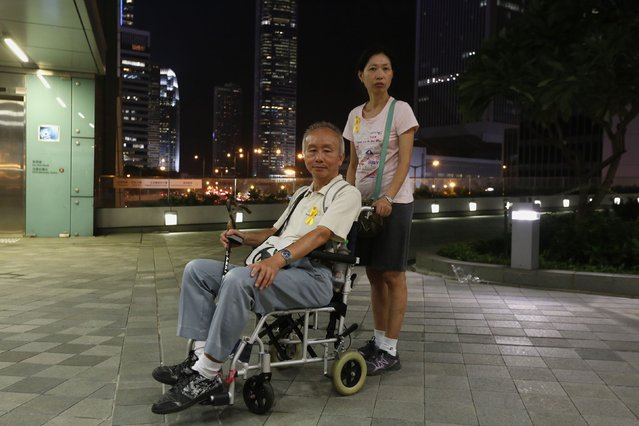 """John Ma (L), 62, a lecturer, and his wife May, 50, pose for a photograph at a rally ahead of an """"Occupy Central"""" civil disobedience protest in Hong Kong September 26, 2014. As a former student leader, Ma said, """"I support student protest and tell them to grab their chance"""". China rules Hong Kong under a """"one country, two systems"""" formula that accords the territory limited democracy. (Photo by Bobby Yip/Reuters)"""