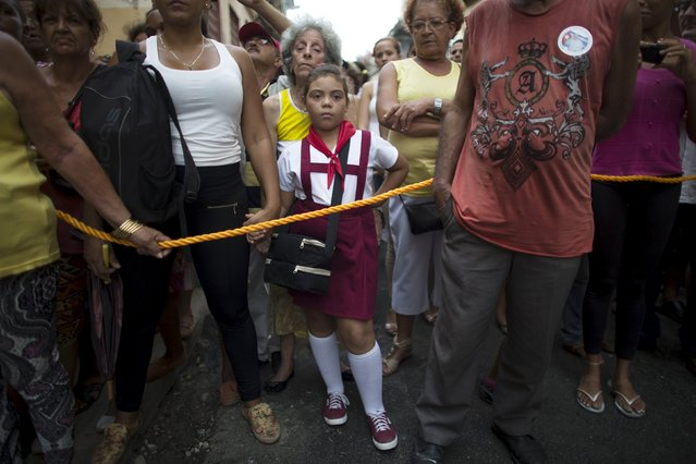 A child waits for the beginning of the annual procession of Our Lady of Charity, the patron saint of Cuba, on the streets of downtown Havana, September 8, 2015. (Photo by Alexandre Meneghini/Reuters)