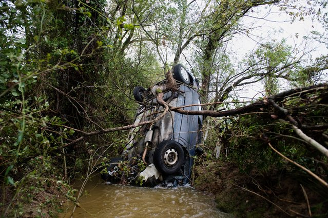 A picture taken on September 30, 2014 shows a crashed car after floodwater streamed down a road in Saint-Pargoire, near Montpellier, southern France.  France declared a state of natural disaster in about 60 southern towns hit by torrential downpours, which also left the Mediterranean city of Montpellier under water. (Photo by Bertrand Langlois/AFP Photo)