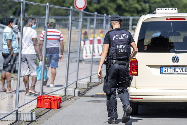 A police officer walks next to apartment buildings that are partly under quarntine due to a new coronavirus outbreak in Verl, Germany, Wednesday, June 24, 2020. After the new  coronavirus outbreak at the meat processor Tönnies in the city of Rheda-Wiedenbrueck, the authorities imposed a lockdown also for the city of Gütersloh and the neighbouring district. (Photo by David Inderlied/dpa via AP Photo)