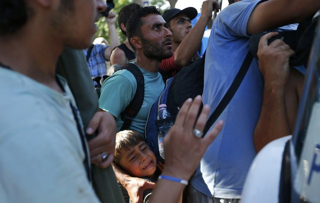 A migrant holds his child as they try to enter a bus at the station in Beli Manastir, Croatia September 18, 2015. (Photo by Laszlo Balogh/Reuters)