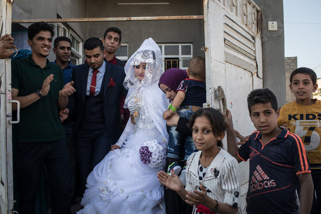Family members watch on as a bride and groom leave their house to be married in West Mosul on November 3, 2017 in Mosul, Iraq. (Photo by Chris McGrath/Getty Images)