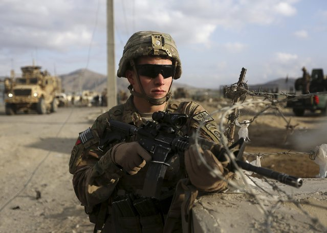 A U.S. soldier keeps watch at the site of a suicide attack in Kabul October 13, 2014. (Photo by Omar Sobhani/Reuters)