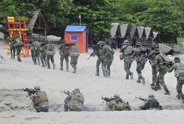 Members of the Marines and Naval Special Operations Groups, take their positions as they move out to rescue hostages from mock rebels during the Fleet-Marine Amphibious Exercise at the marine headquarter in Ternate, cavite city, south of Manila September 24, 2015. (Photo by Romeo Ranoco/Reuters)