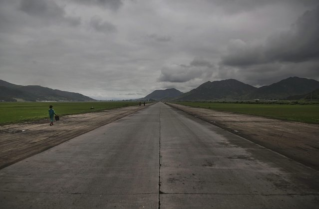 In this June 21, 2014 photo, a woman walks along an open road southeast of Pyongyang in North Korea's North Hwanghae province. (Photo by David Guttenfelder/AP Photo)