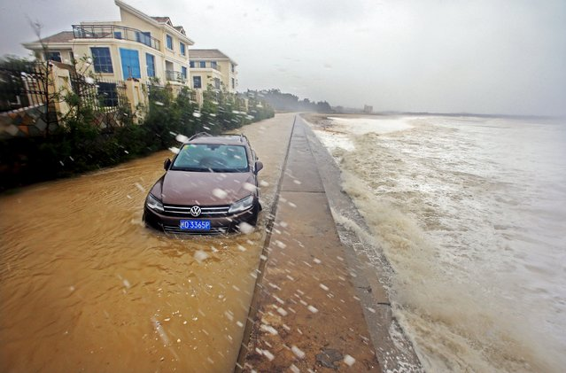 A car is trapped as waves brought by Typhoon Dujuan slam the coastline in Quanzhou, Fujian province, September 29, 2015. (Photo by Reuters/Stringer)