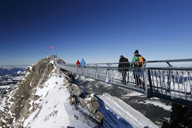 """Guests walk along the """"Peak Walk"""" bridge during a media preview, at the Glacier 3000 in Les Diablerets October 24, 2014. (Photo by Denis Balibouse/Reuters)"""