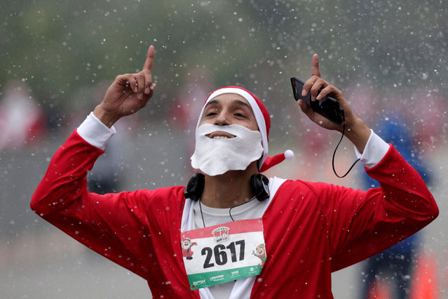 "A participant dressed up as Santa gestures as he arrives at the finish line during the annual race know as ""Run Santa Run"" at Fundidora Park in Monterey, Mexico December 17, 2017. (Photo by Daniel Becerril/Reuters)"