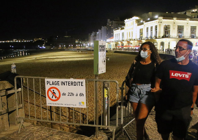 People wear face masks as they walk near the closed beach in Biarritz, southwestern France, Wednesday, August 5, 2020. Biarritz beach is closed all night from 10 p.m. to 6 a.m. to avoid beach youth gatherings and the spread of COVID-19. (Photo by Bob Edme/AP Photo)