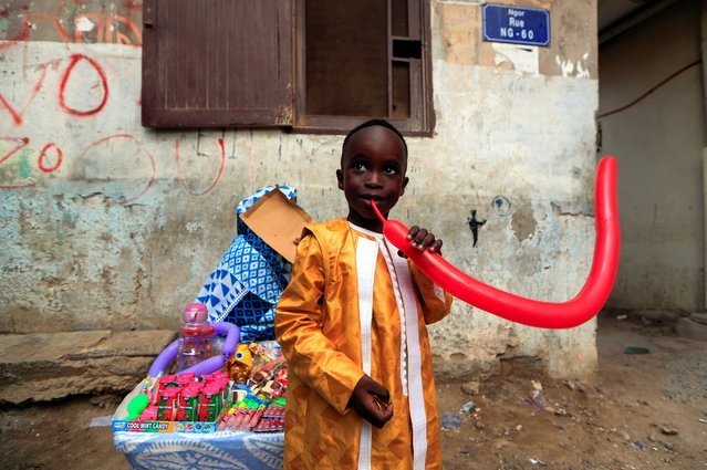 A boy tries to inflate a balloon that he just bought during the celebration of the first day of Eid al-Adha in Dakar, Senegal on July 31, 2020. (Photo by Zohra Bensemra/Reuters)