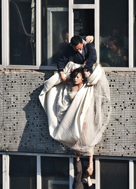 A 22-year-old woman in a wedding gown is grabbed by Guo Zhongfan, a local community officer, as she attempts to kill herself by jumping out of a seven-storey residential building in Changchun, Jilin province. According to local media, the woman tried to commit suicide after her boyfriend of four years broke up with her, just as they were making plans to get married. The woman did not sustain any injuries during the incident. (Photo by China Daily/Reuters)