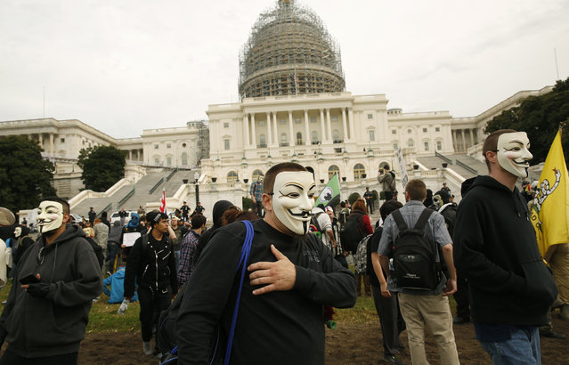 Members and supporters wearing Guy Fawkes masks depart the U.S. Capitol in Washington November 5, 2014. (Photo by Gary Cameron/Reuters)