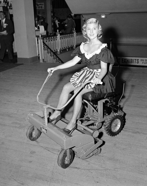 "This power lawn mower is one of the new products, large and small, on display at the National Hardware Show in New York, October 8, 1952. Claudia Hall presents the mower which has these features: a 30-inch cutting width, same transmission and differential as an automobile, short wheel base for high maneuverability, cutting speed up to six miles an hour or a rate of an acre of cutting an hour. The power unit is detachable for use elsewhere. The machine, called the 'Hoko"", is manufactured by the Western Tool and Stamping Co. of Des Moines, Iowa. (Photo by Robert Kradin/AP Photo)"