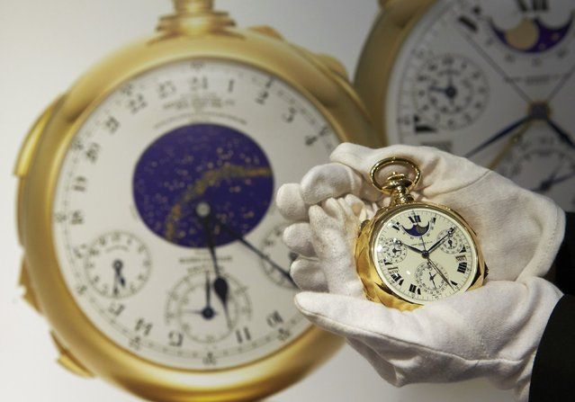 "A staff member holds ""The Henry Graves Supercomplication"" handmade watch by Patek Philippe at Sotheby's auction house in Geneva November 5, 2014. This masterpiece of horology, which was completed in 1932, is estimated to sell in excess of close to 15,000,000 Swiss Francs (US $ 15,544,000) when it is auctioned on November 11 in Geneva. (Photo by Denis Balibouse/Reuters)"