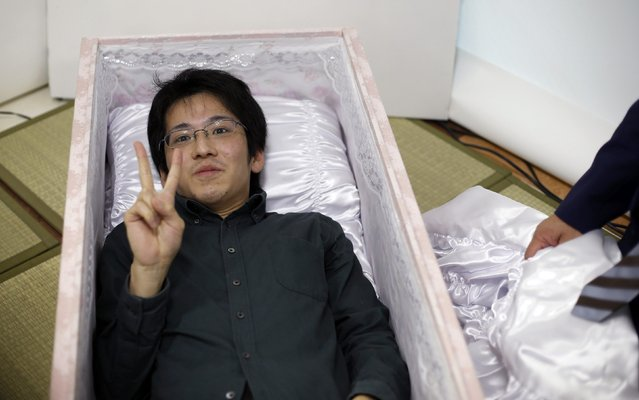 Noriaki Iwashima gestures as he lies in a coffin to try it out during an end-of-life seminar held by Japan's largest retailer Aeon Co in Tokyo October 24, 2014. (Photo by Toru Hanai/Reuters)
