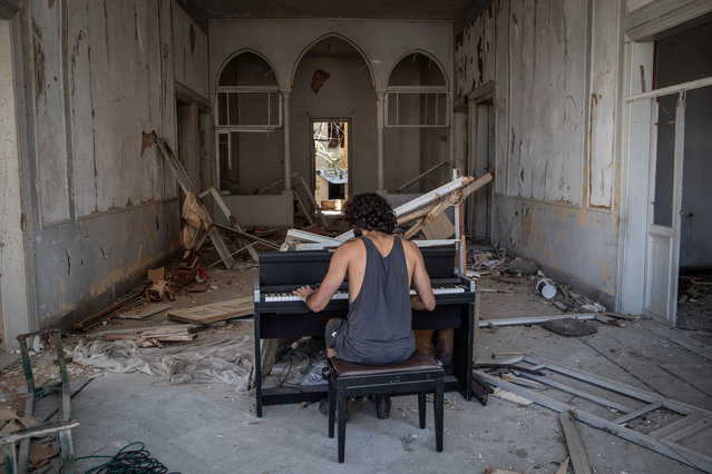 Artist and musician Raymond Essayan plays a piano he partly sculpted into the shape of a grand piano from the rubble in a destroyed building while shooting a music video for the piece he wrote to be released in dedication to Beirut after the past week's explosion on August 14, 2020 in Beirut, Lebanon. Raymond suffered a concussion and his home was destroyed during the port explosion, although he started to write the musical piece in 2018 he decided to finish it and shoot a music video to release it now after the Beirut port explosion. The explosion at Beirut's port last week killed over 200 people, injured thousands, and upended countless lives. There has been little visible support from government agencies to help residents clear debris and help the displaced, although scores of volunteers from around Lebanon have descended on the city to help clean. (Photo by Chris McGrath/Getty Images)