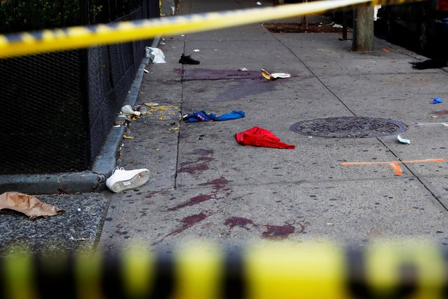 A blood stained sidewalk and clothing are seen behind NYPD police tape, where according to local media reports five people were shot, including a 6-year-old boy, early Monday during an outdoor J'Ouvert celebration, in the Crown Heights section Brooklyn in New York, U.S., September 7, 2020. (Photo by Shannon Stapleton/Reuters)