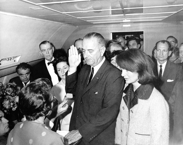 Flanked by Jacqueline Kennedy (right) and his wife Lady Bird Johnson (2nd left), U.S Vice President Lyndon Johnson is administered the oath of office by Federal Judge Sarah Hughes, as he assumed the presidency of the United States, on November 22, 1963, following the assassination of President John F. Kennedy in Dallas (Photo by Cecil Stoughton/AFP Photo)