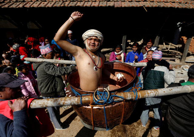 A devotee sprinkles water, considered holy, while being carried around the town in a vessel as part of rituals during the Swasthani Brata Katha festival in Thecho, Lalitpur, Nepal January 28, 2018. (Photo by Navesh Chitrakar/Reuters)