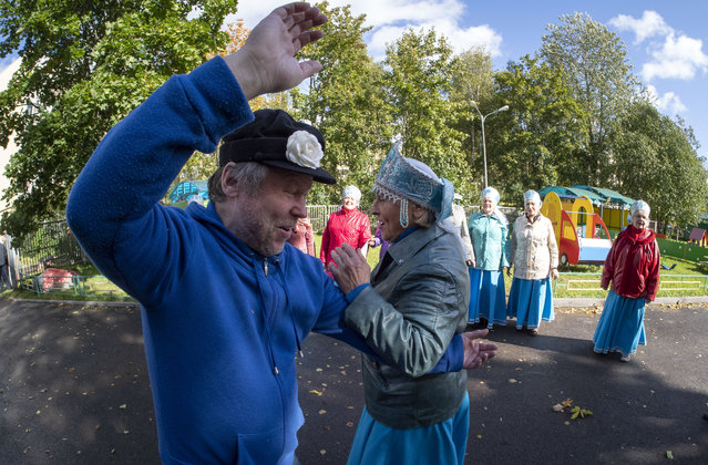 People dance near a poling station during Leningrad region's governor and municipal elections, in Luppolovo village, outside St. Petersburg, Russia, Sunday, September 13, 2020. (Photo by Dmitri Lovetsky/AP Photo)