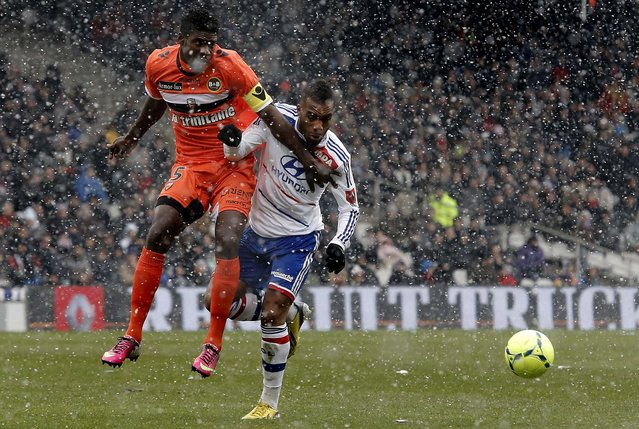 Lyon's Alexandre Lacazette, right, challenges for the ball with Lorient's Bruno Ecuele Manga during their French League One soccer match at Gerland stadium in Lyon, France, on February 24, 2013. (Photo by Laurent Cipriani/Associated Press)