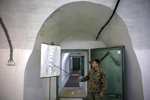 A member of the armed forces of Bosnia and Herzegovina shows a map of Tito's underground secret bunker (ARK) in Konjic, October 16, 2014. (Photo by Dado Ruvic/Reuters)