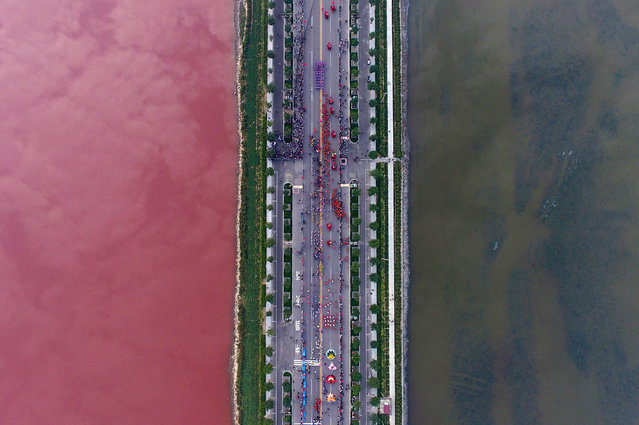 A salt lake which is separated by a road, shows parts of it in different colours due to algae, in Yuncheng, Shanxi Province, China, September 25, 2016. (Photo by Wei Liang/Reuters)