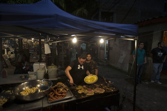 A couple sells roast meat near where anti-government demonstrators gather to protest at the Hato neighborhood in Tegucigalpa, Honduras, Friday, December 8, 2017. (Photo by Moises Castillo/AP Photo)