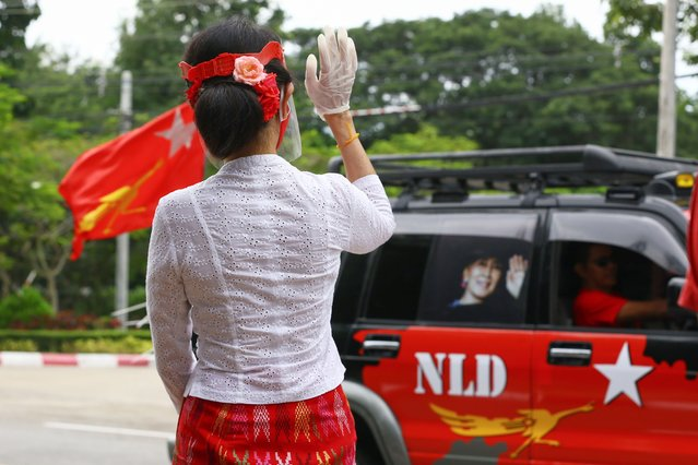 Myanmar's de-facto leader Aung San Suu Kyi wearing a facemask and gloves, to halt the spread of the COVID-19 coronavirus, waves to supporters of her National League for Democracy (NLD) party as they drive past in Naypyidaw on September 19, 2020. (Photo by Thet Aung/AFP Photo)