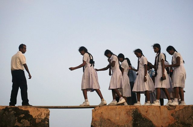 School girls walk across a plank on the walls of the 16th century Galle fort, Sri Lanka, on July 8, 2009. (Photo by Vivek Prakash/Reuters)