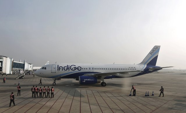Indigo Airlines' ground staff stand next to an aircraft after it arrived at the Srinagar airport November 21, 2014. (Photo by Adnan Abidi/Reuters)