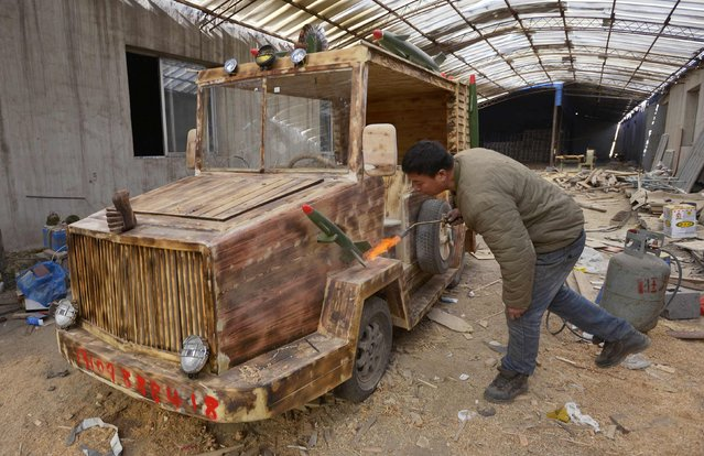 Carpenter Liu Fulong, 48, torches his homemade wooden electric car for a vintage look at his workshop in Shenyang, Liaoning province December 5, 2014. The 2.5m long, 1.3m wide car, decorated with fake missiles and radar, cost Liu about 20,000 yuan ($3,252 USD) and took 4 months to complete. It is the second wooden vehicle he has made and weighing over 350kg (772 lbs) it has a maximum speed of 50km per hour, local media reported. (Photo by Reuters/Stringer)