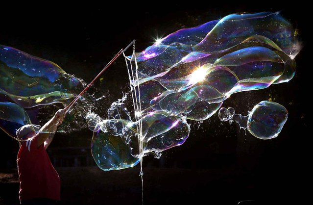 Paul Pedro, of Springfield, Ore., creates a flying cloud of soap bubbles at Skinner Butte Park in Eugene, Ore., Tuesday September 8, 2015. He was using custom sticks and ropes to make elaborate and ever changing bubble creations to the delight of visitors to the park. (Photo by Chris Pietsch/The Register-Guard via AP Photo)
