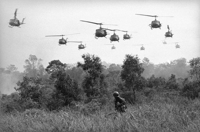 Hovering U.S. Army helicopters pour machine gun fire into tree line to cover the advance of Vietnamese ground troops in an attack on a Viet Cong camp 18 miles north of Tay Ninh on March 29, 1965, which is northwest of Saigon near the Cambodian border. Combined assault routed Viet Cong guerrilla force. (Photo by Horst Faas/AP Photo)