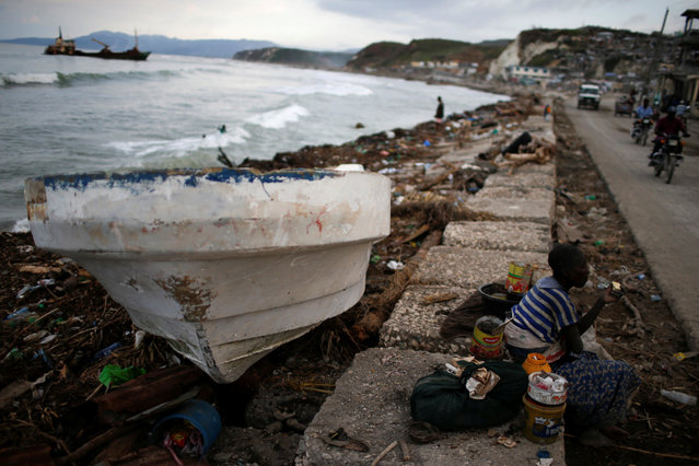 A woman eats next to a boat after Hurricane Matthew hit Jeremie, Haiti, October 15, 2016. (Photo by Carlos Garcia Rawlins/Reuters)